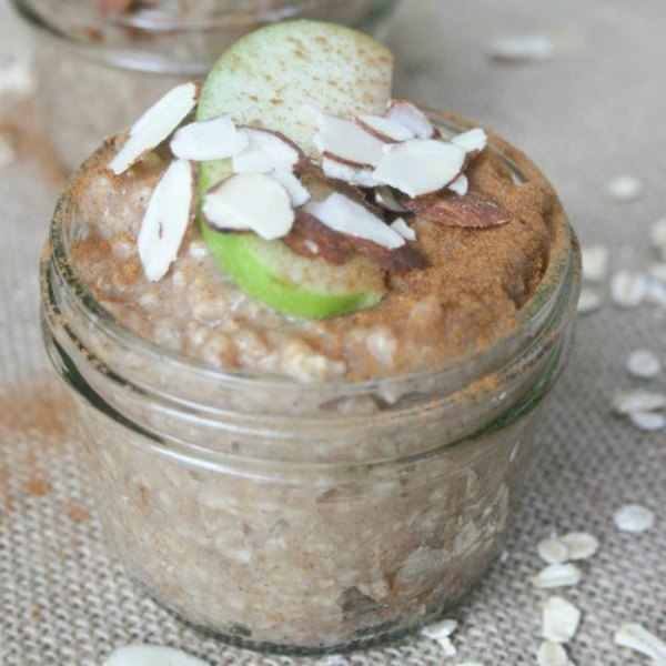 oats in a glass jar with sliced almond and green apples on top