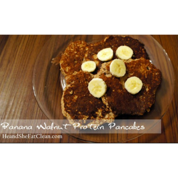 pancakes with banana slices on top placed on a clear plate on a wooden table