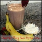 chocolate protein shake in a glass cup with a strawberry on top and banana and cottage cheese in front