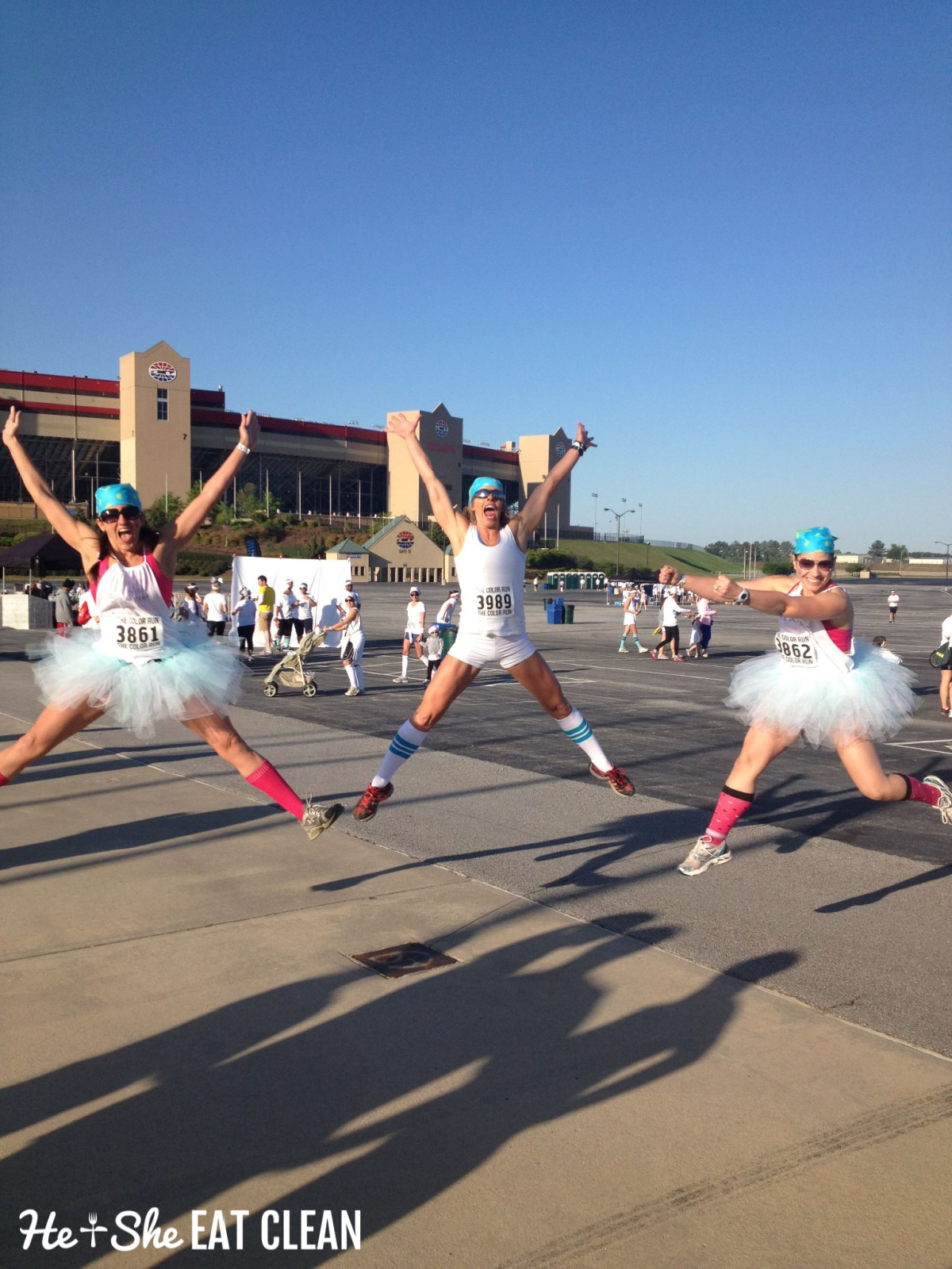 3 females jumping in the air wearing tutus before the start of the color run