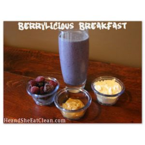 blueberry protein shake in a glass on a wooden table with berries, peanut butter, and protein powder