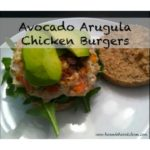 chicken burger with avocado and arugula on top on a white plate