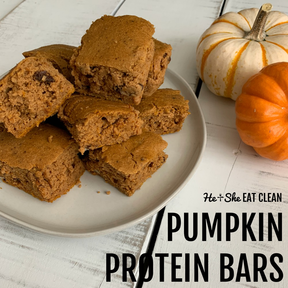 stack of pumpkin protein bars on a white plate with 2 small pumpkins behind the plate square image