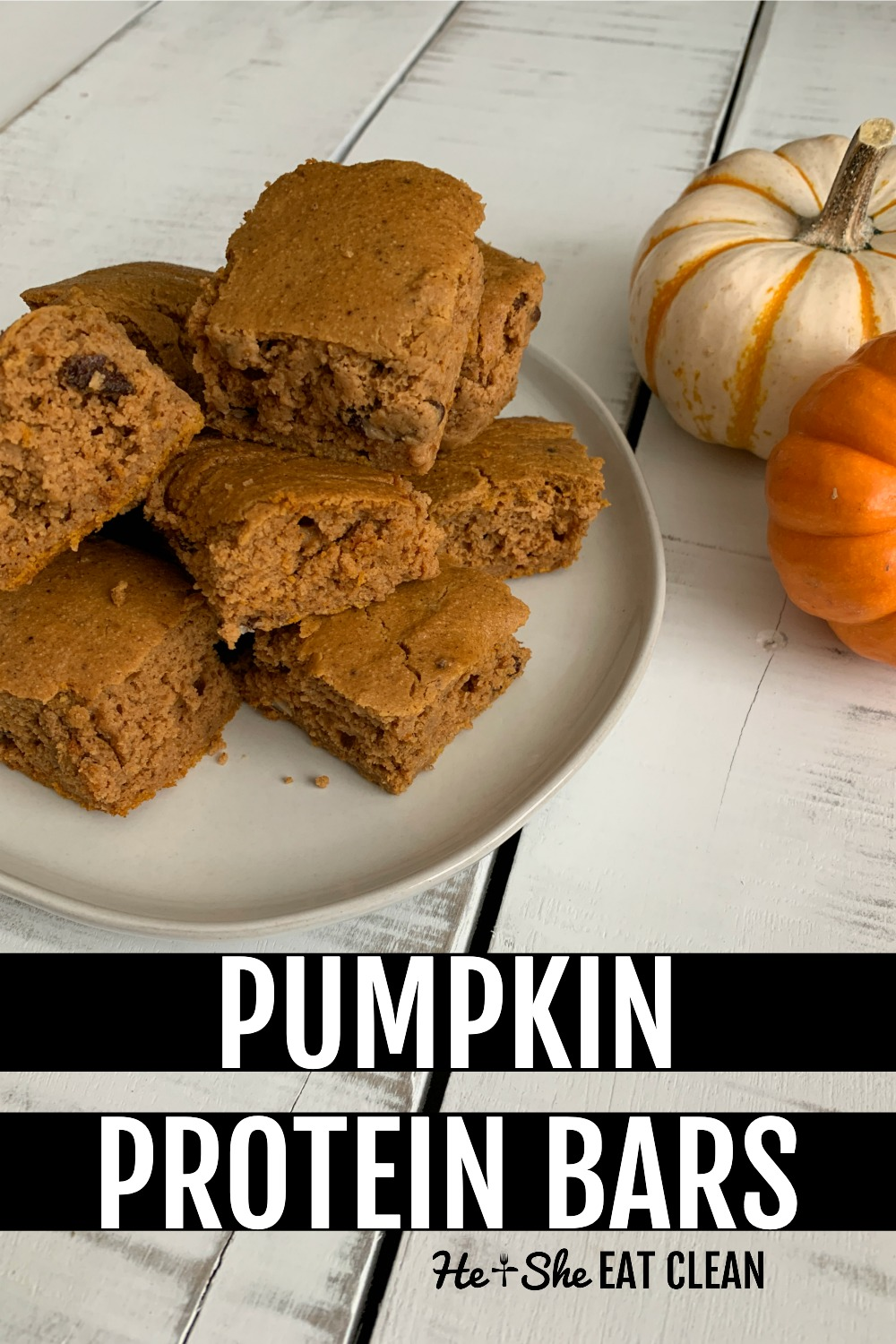 stack of pumpkin protein bars on a white plate with 2 small pumpkins behind the plate