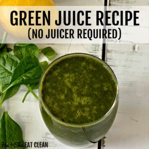 glass of green juice on a white table with spinach and lemon in the background