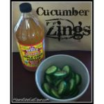 cut up cucumber in a white bowl with a bottle of Apple Cider Vinegar behind it