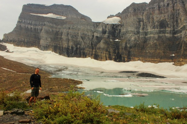 male standing next to a glacier before hiking Grinnell Glacier in Glacier National Park, Montana