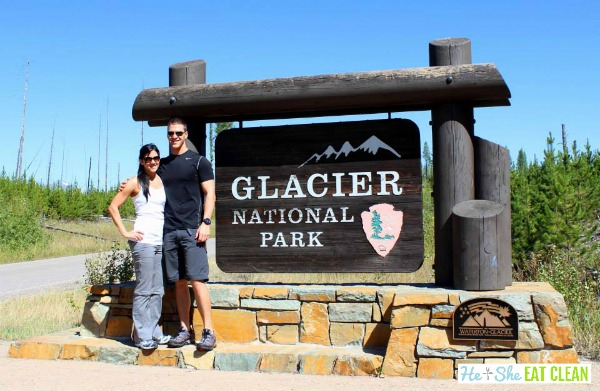 male and female standing in front of Glacier National Park entrance sign
