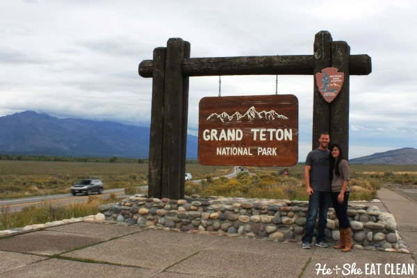 male and female standing next to the Grand Teton national park sign