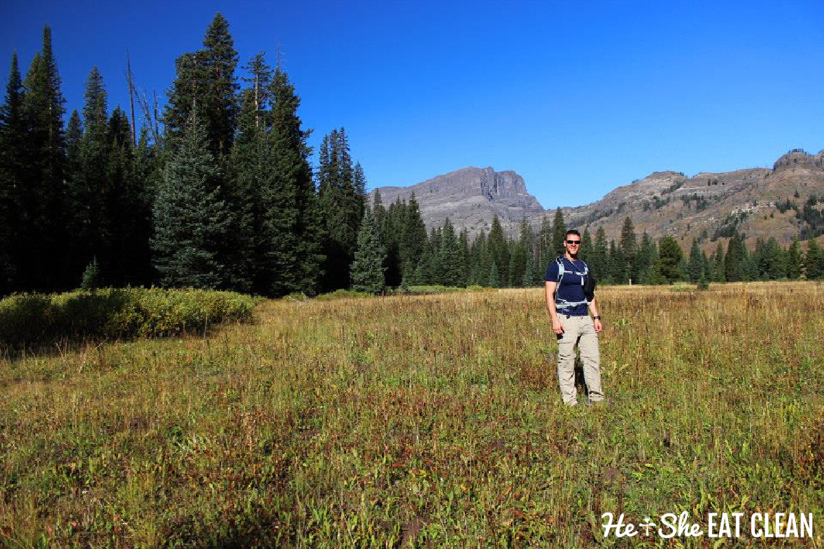 male standing in a meadow wearing a black shirt and beige hiking pants