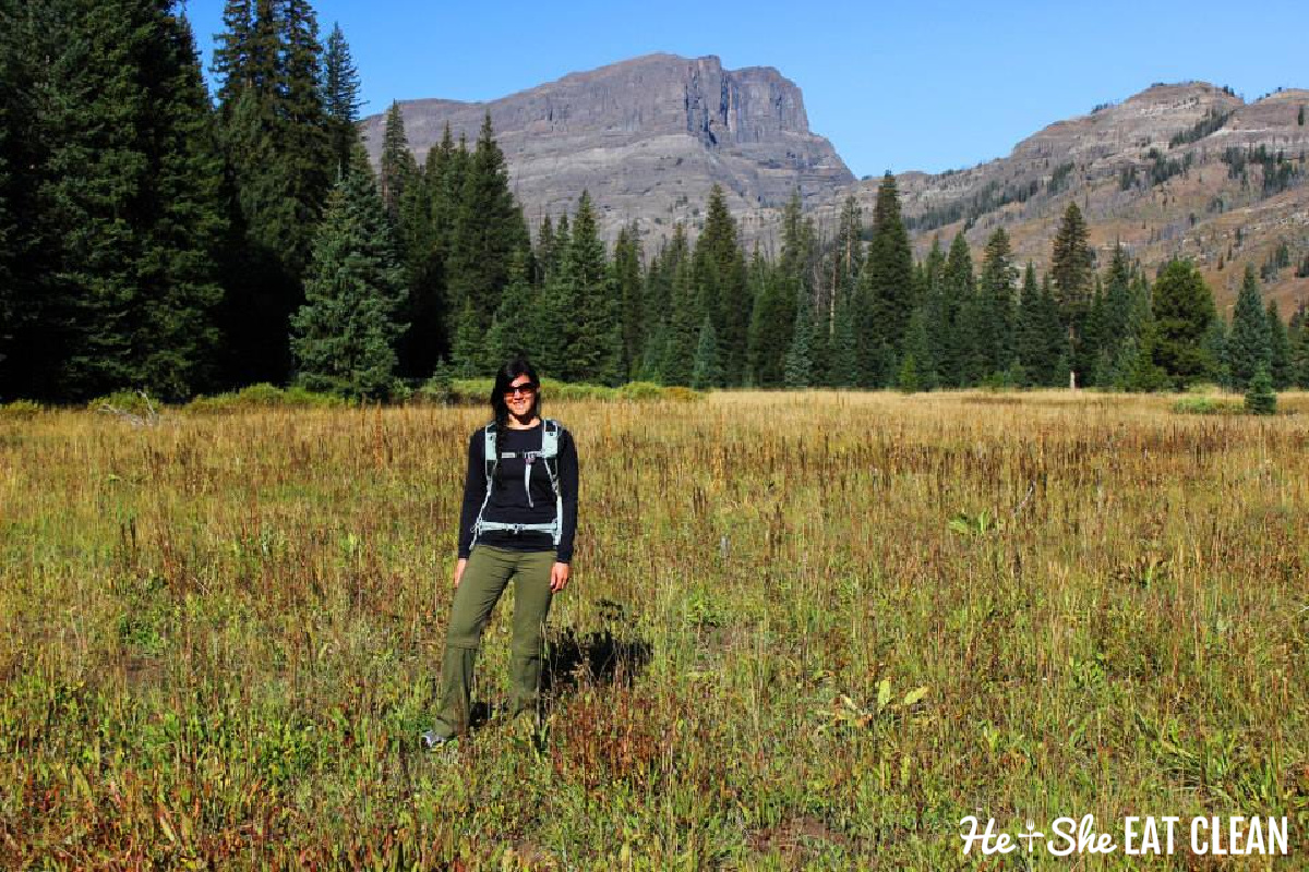female standing in a meadow with a black top & green hiking pants
