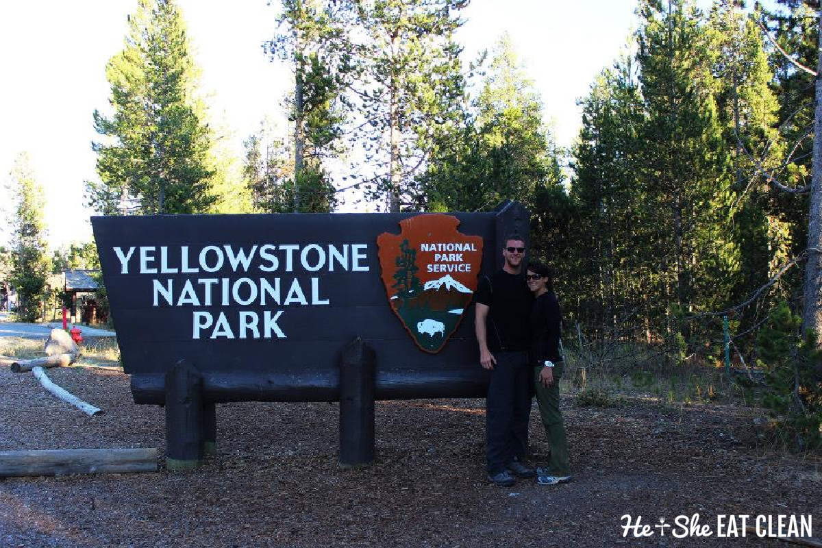 male and female couple standing to the right side of a sign that reads Yellowstone National Park