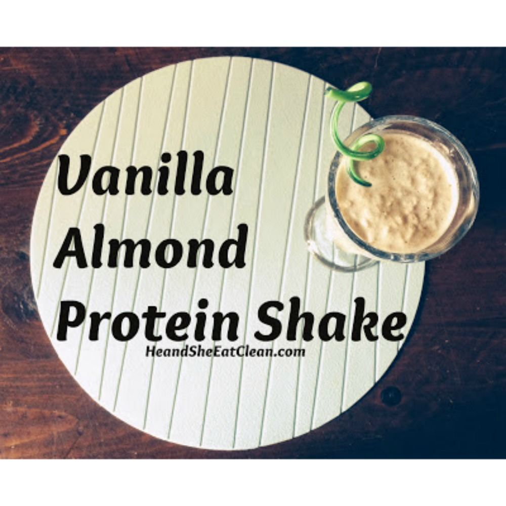 vanilla almond protein shake in a clear glass on a blue placemat