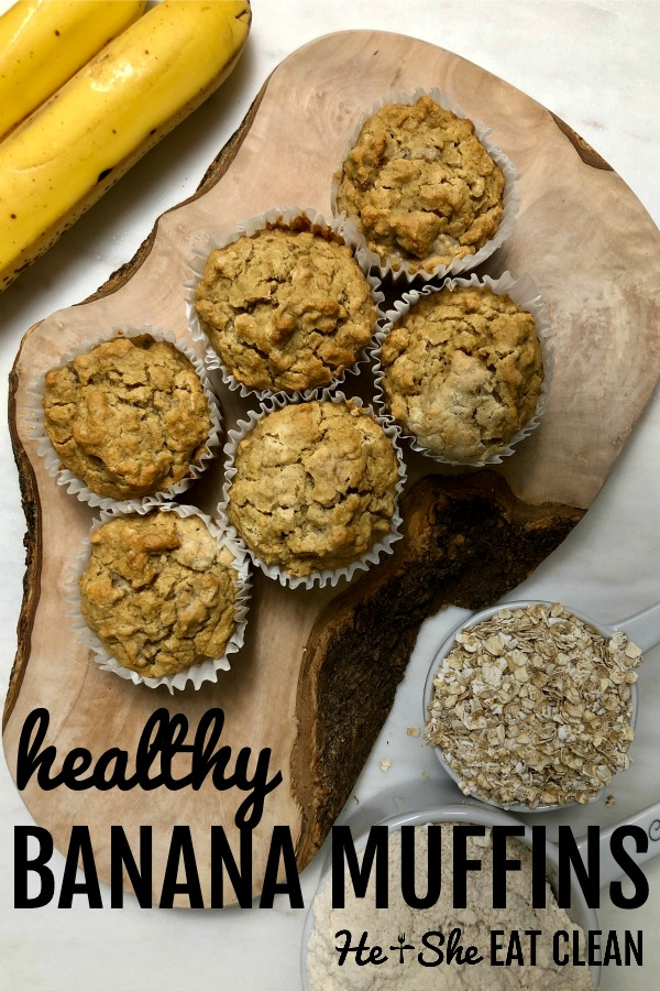 6 banana muffins on a wooden board with bananas in the background and oats and oat flour to the side