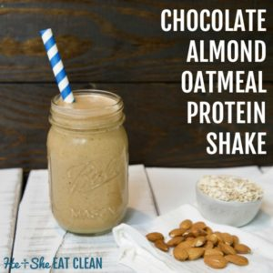 almond protein shake in a glass mason jar with a blue straw on a white wooden plank board with almonds and oats