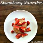 stacked pancakes topped with strawberries on a white place