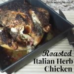 roasted chicken in a black pan on a beige table with a knife