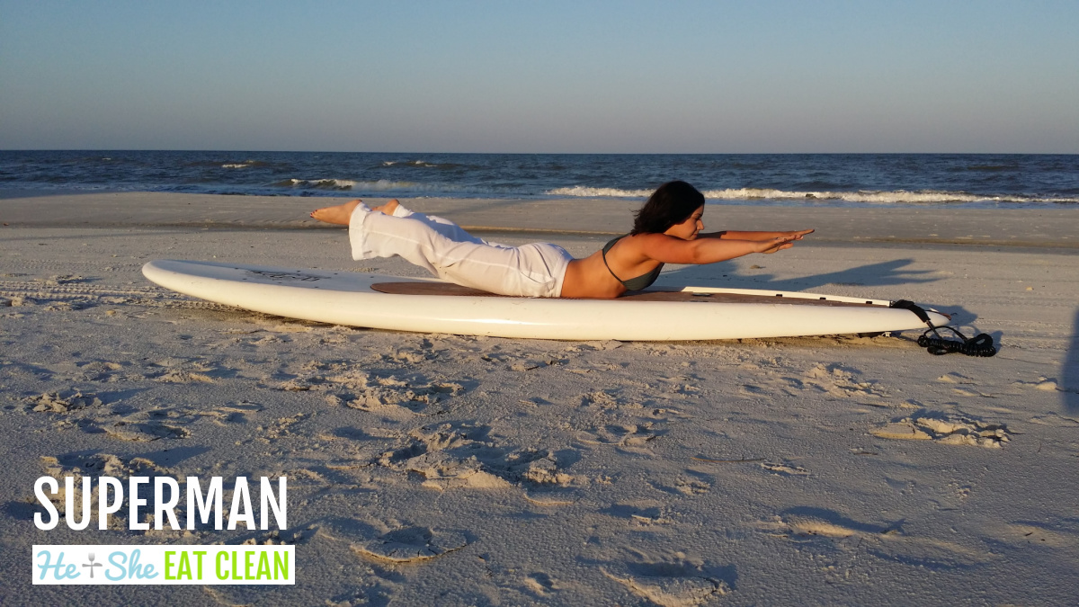 female on a paddleboard on the beach doing a superman exercise with arms and legs raised