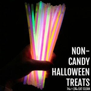 female hand holding a bunch of lit up glowsticks with text that reads non candy Halloween treats square image