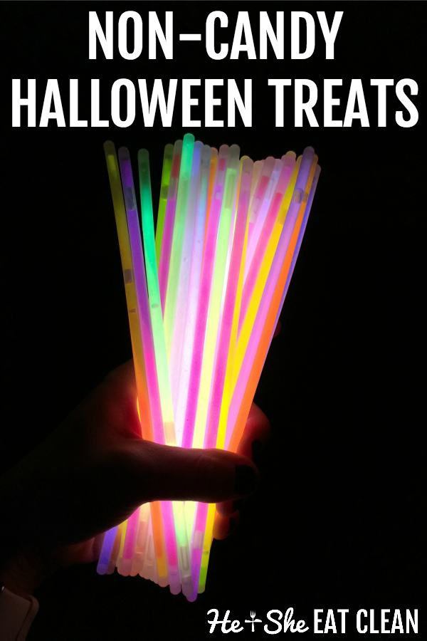 female hand holding a bunch of lit up glowsticks with text that reads non candy Halloween treats