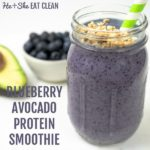 smoothie in a mason jar with granola on top with text that reads blueberry avocado protein smoothie with avocado and blueberries in the background