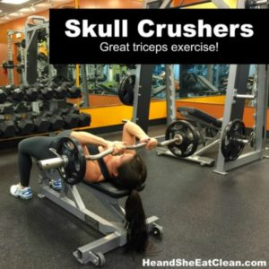 woman lying on a bench doing a skull crushers exercise