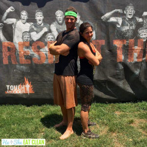 male and female standing back to back after the Tough Mudder race event