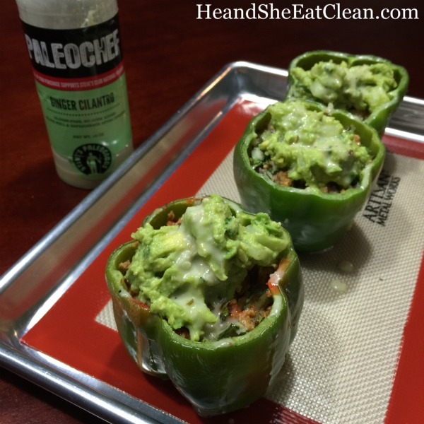 3 green peppers stuffed with meat and topped with avocado on a baking sheet