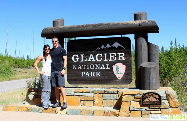 male and female standing next to glacier national park entrance sign