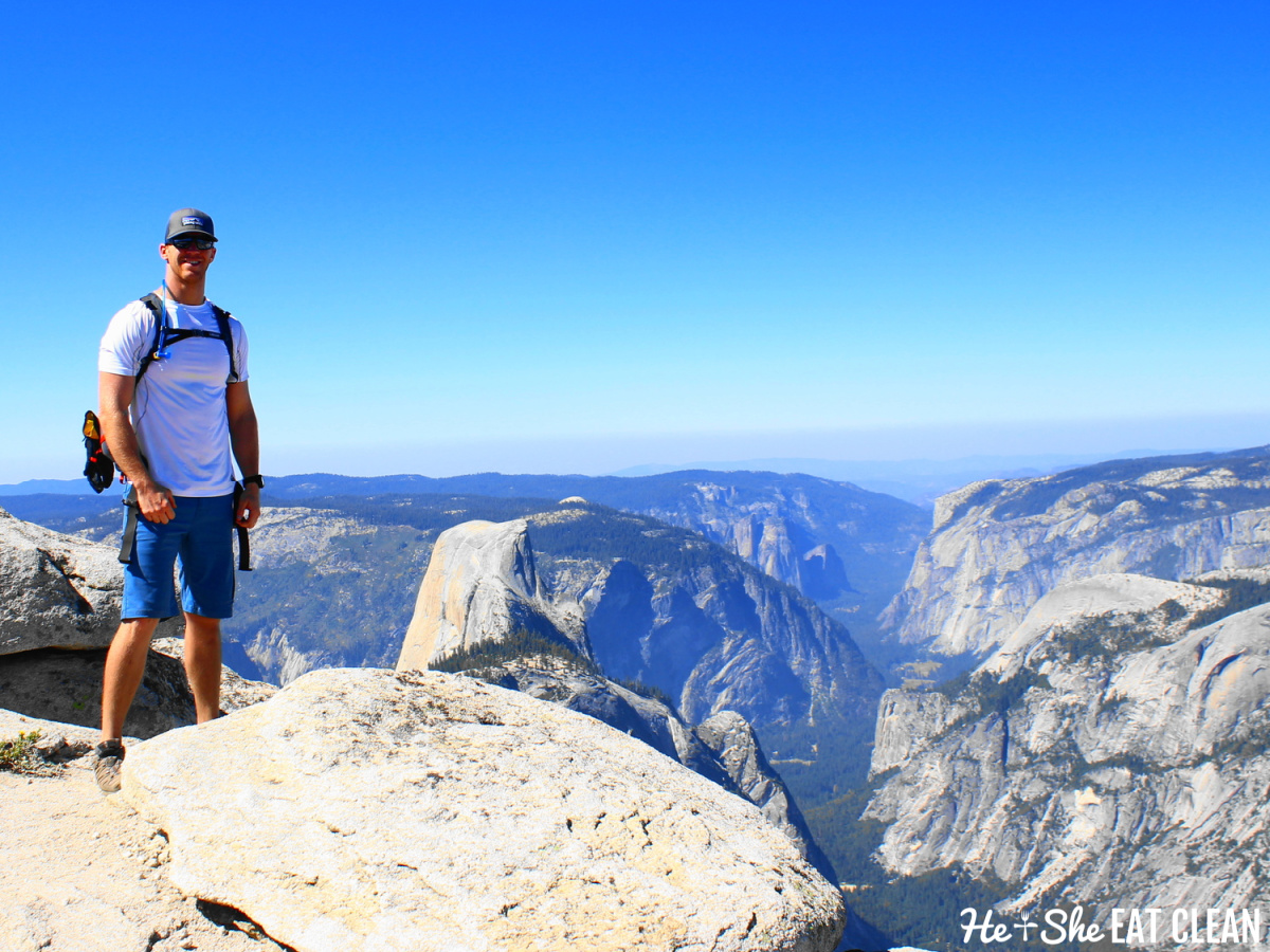 male standing at the summit of Clouds Rest in Yosemite National Park with Half Dome in the background