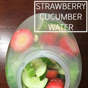 jug filled with water and strawberries and cucumbers on a wooden table