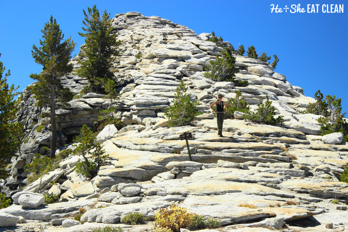 female hiker standing right before the summit of Clouds Rest in Yosemite National Park - rocks and small trees on the mountaintop