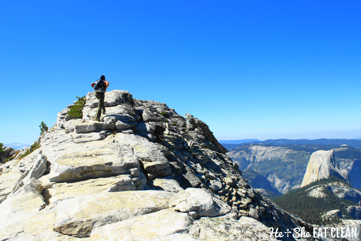 female summiting Clouds Rest in Yosemite National Park. Mountains, rocks and trees in the picture
