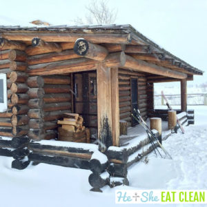 log wood cabin with snow and skis leaning on the front porch