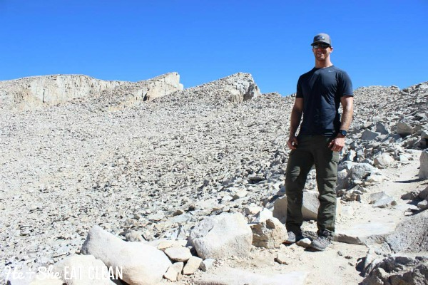 male standing on rocks on top of Mount Whitney in California