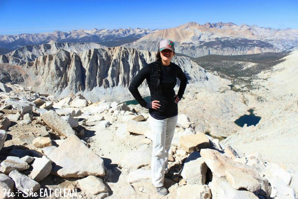 female standing on rocks on top of Mount Whitney in California