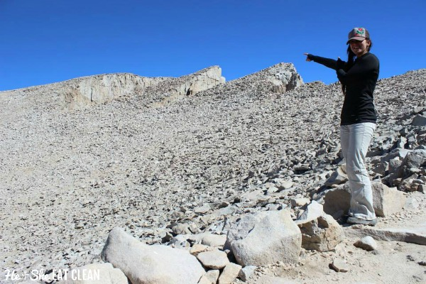 female standing on rocks on top of Mount Whitney in California pointing to the top of the mountain