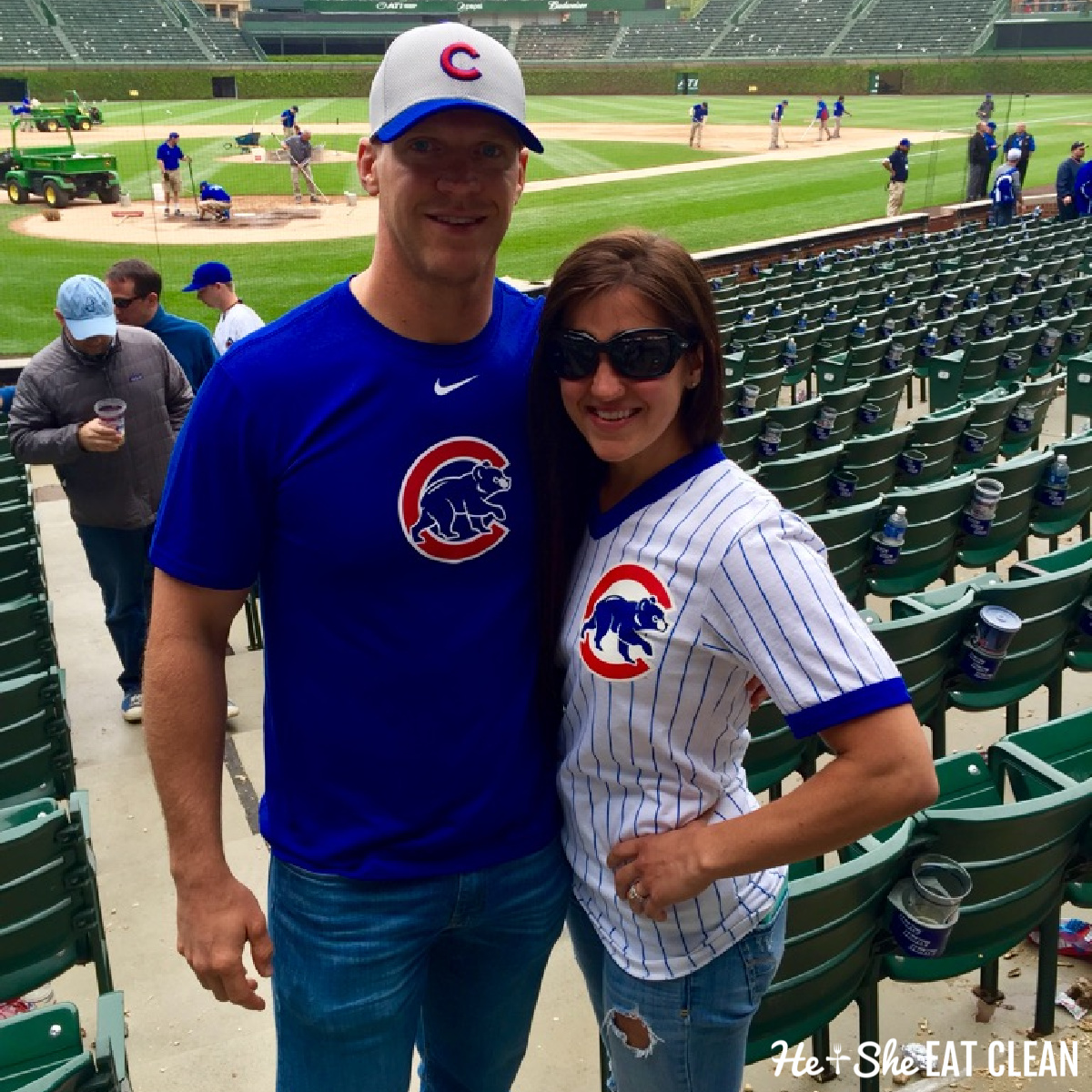 male and female standing behind home plate at Wrigley field wearing Cubs gear
