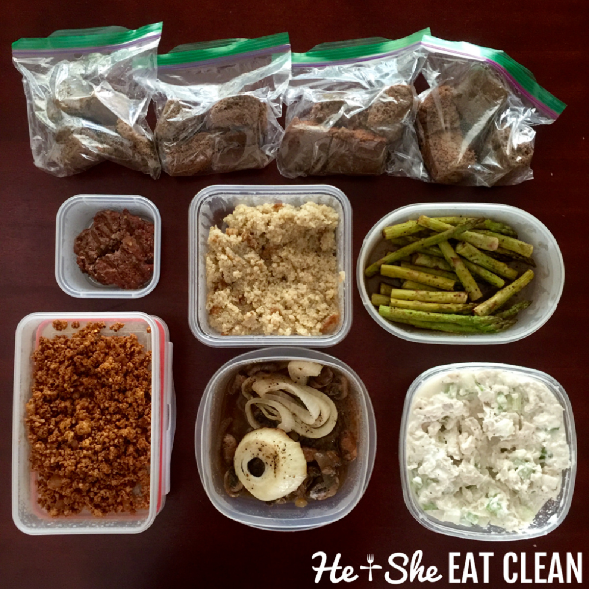 overhead shot of clean eating food prep: protein bars, chicken, burgers, asparagus, chicken salad