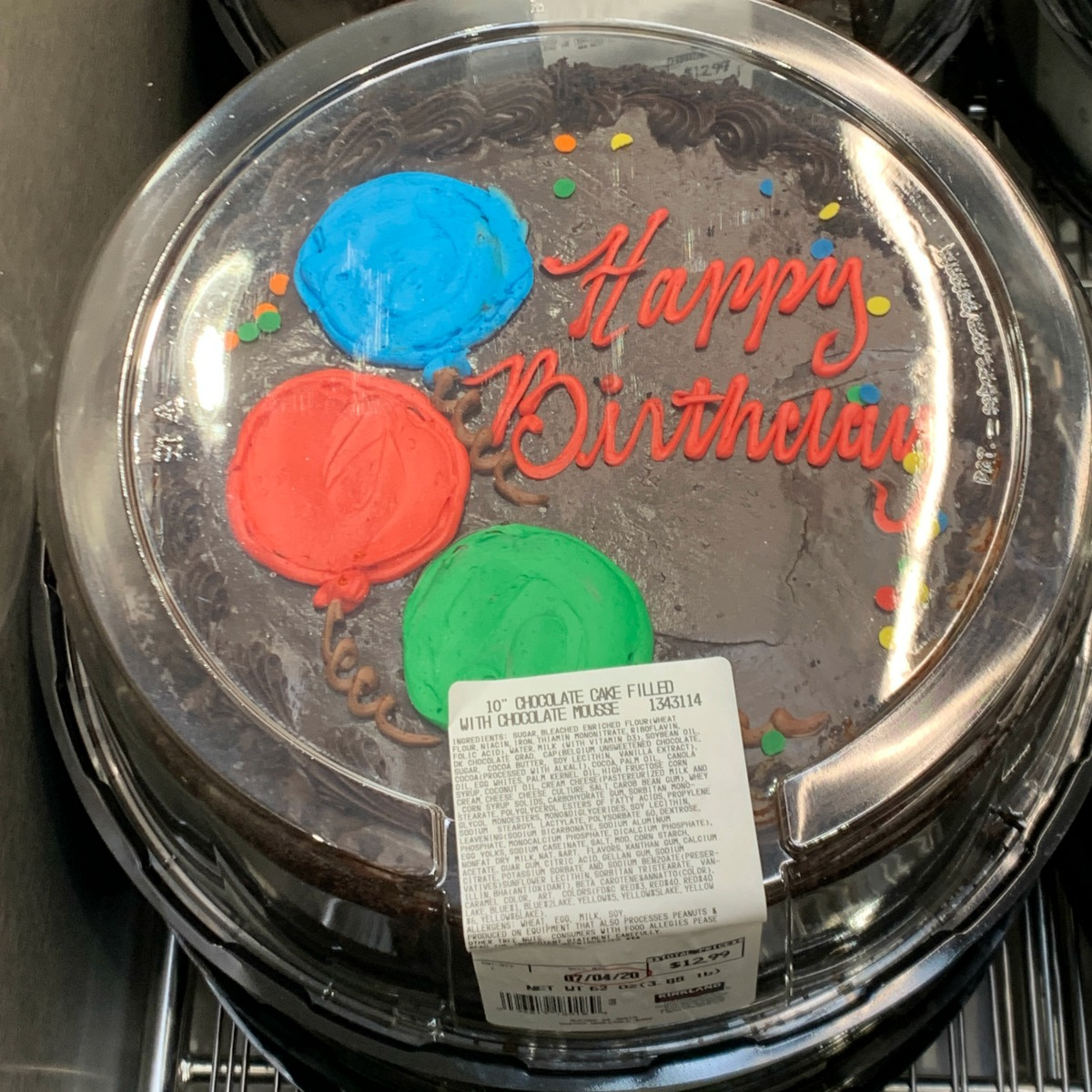 chocolate cake from Costco that reads Happy Birthday with balloons