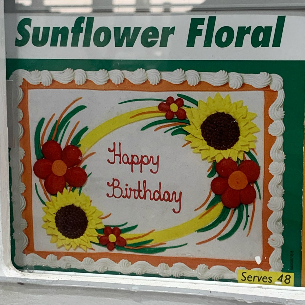 Costco Cake: white frosting, text reads Happy Birthday with sunflowers