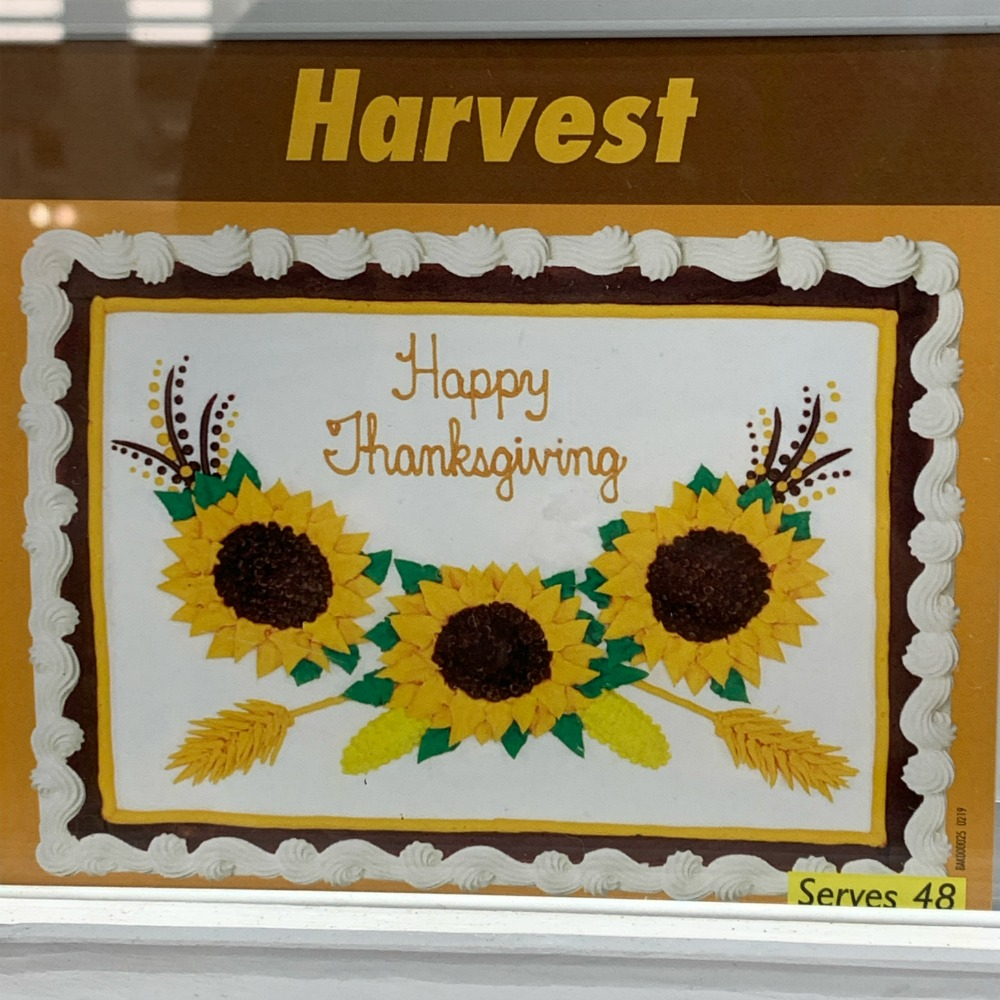 Costco Cake: white frosting, text reads Happy Thanksgiving with sunflowers