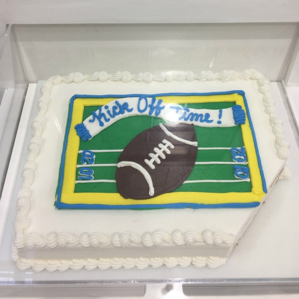 Super Bowl Football Costco Cake Design - cake with white icing and a football and banner that says kick off time