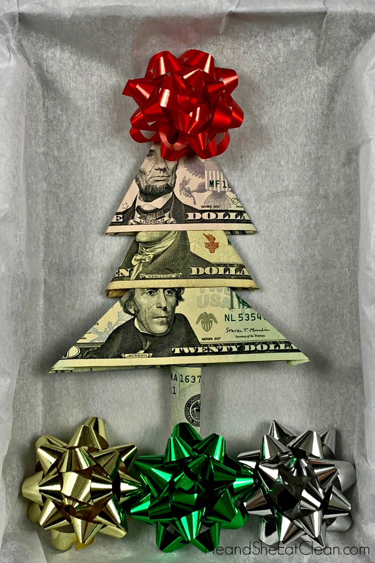 Christmas tree shape made out of bills with bows placed around it as the ground and tree topper