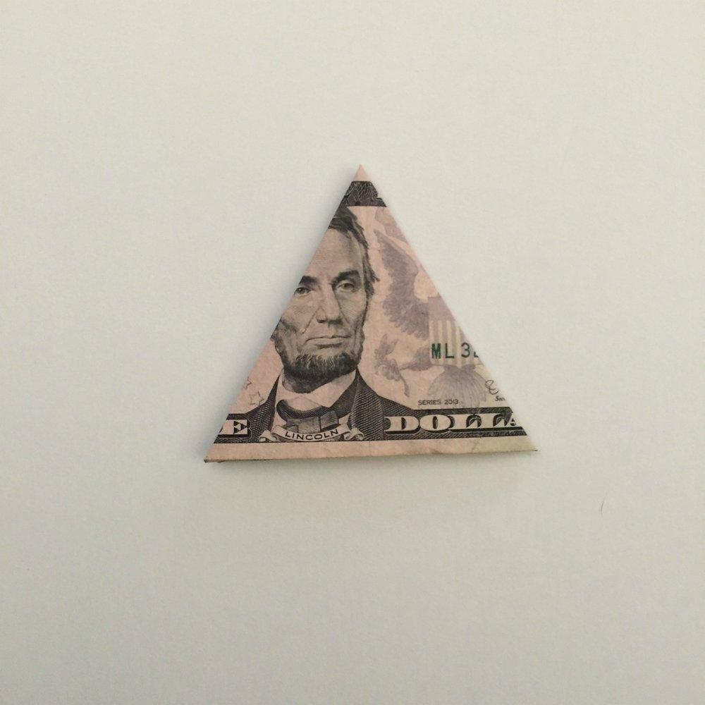 5 dollar bill folded as step 3 to make a money tree