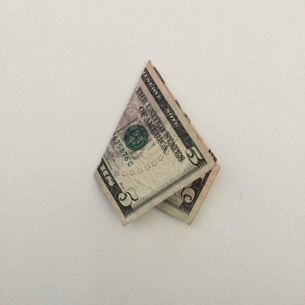 5 dollar bill folded as step 2 to create Christmas money tree
