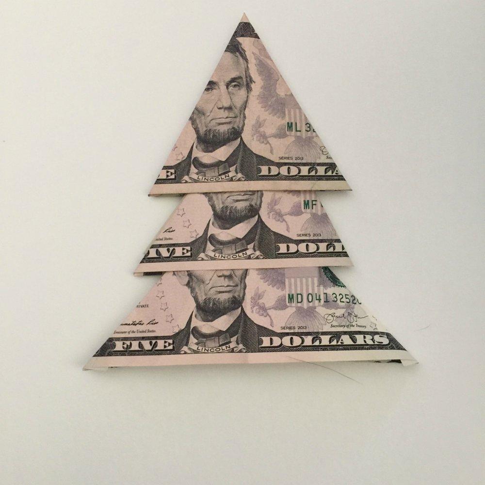 3 five dollar bills folded to make a Christmas money tree step 6