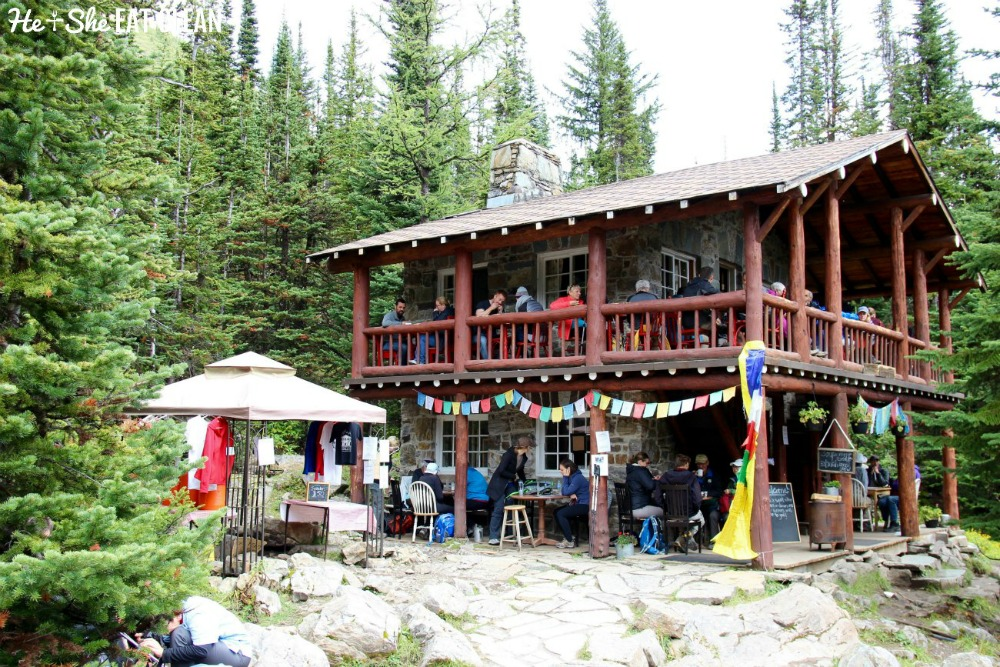 log cabin with flags on the deck and people eating at Plain of Six Glaciers Tea House in Banff National Park