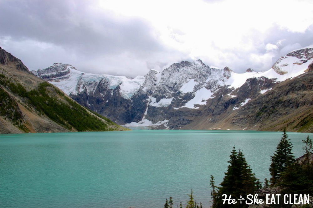 landscape photo of a aqua green lake of water with snowcapped mountains in the background on the Lake of the Hanging Glacier trail