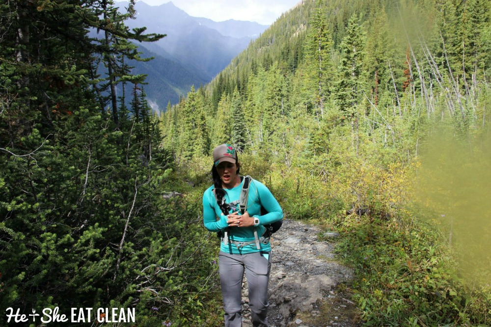 female hiker on a trail with green trees and mountains in the background on Lake of the Hanging Glacier hike